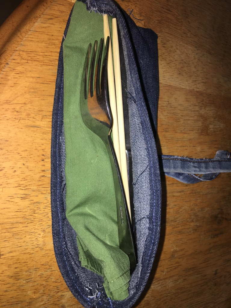 photo of a denim cutlery case filled with a green napkin, chopsticks, and silverware.